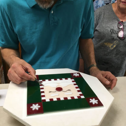 Fused christmas cookie tray class Steve Trebacz making final adjustments before firing student santa project