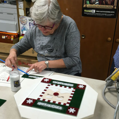 Fused christmas cookie tray class student placing glass frit on Santa project