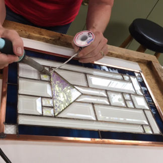 Student soldering stained glass project